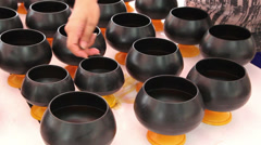 People merit some coins to into Monk's alms bowl Stock Footage