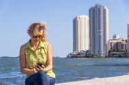 Stock Photo of usa, florida, miami, mature woman sitting on surrounding wall of port and usi