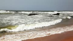 Pan shot of moving waves with tourists on the Ramakrishna Beach Stock Footage