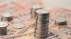 Stack of coins on Indian banknotes - stock footage