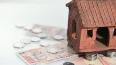 Pan Shot of a clay house with coins and Indian banknotes Stock Footage