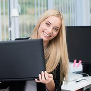 smiling office worker holding a laptop - stock photo