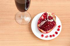 goblet of wine and a pomegranate on the table - stock photo