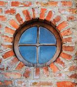 Round window on brick wall on castle Stock Photos