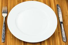 white plate, knife and fork at bamboo napkin - stock photo