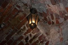 old red bricks wall and light hanging on the wall - stock photo