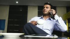 Shot of a businessman talking on a mobile phone and having coffee Stock Footage
