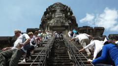 Tourists climbing up steep steps leading to the Central Sanctuary of Angkor Wat Stock Footage