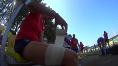 Rugby player bandaging her leg with  tape Stock Footage