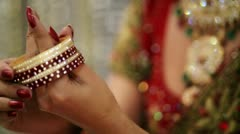 Shot of a Indian bride putting on bangles in her hand - stock footage