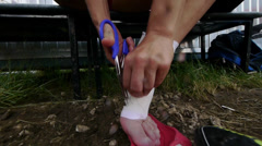 Rugby player with scissors cuts off  the bandage from the foot. Stock Footage