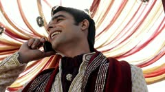 Shot of a Indian groom in traditional wedding dress talking on a mobile phone Stock Footage