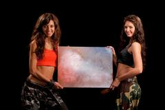 Image of a two girls holding a table Stock Photos
