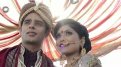 Shot of Indian bride and groom in traditional wedding dress under a mandap - stock footage