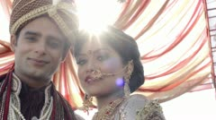 Shot of Indian bride and groom in traditional wedding dress under a mandap Stock Footage