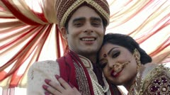 Indian bride and groom in traditional wedding dress posing under a mandap - stock footage