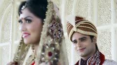 Rack focus shot of Indian bride and groom smiling and posing Stock Footage