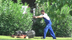 Workers cutting grass with lawnmower, trimmer, employees working, summer jobs Stock Footage