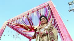 Locked-on shot of a Indian bride smiling and posing under a mandap Stock Footage