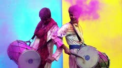 Locked-on shot of two male friends celebrating Holi with playing dhol Stock Footage