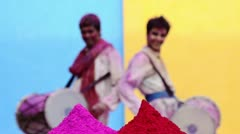 Rack focus shot of two male friends playing dhol during holi festival Stock Footage