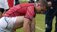 Rugby player with a tattoo on his leg lace shoes. Stock Footage