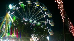 Locked-on shot of Ferris wheel and dragon boat ride in a fair Stock Footage