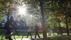 Couple walking and cyclist in the park - pan Stock Footage