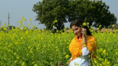 Locked-on shot of a woman talking on a mobile phone in a mustard field Stock Footage
