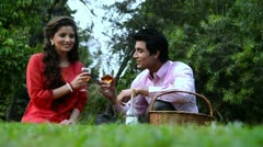 Locked-on shot of a couple feeding wine to each other in a park Stock Footage