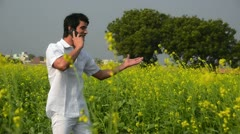 Locked-on shot of a man talking on a mobile phone in a mustard field Stock Footage