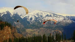 Locked-on shot of paragliders over mountain range - stock footage