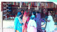 Pan shot of women shopping at a market stall - stock footage