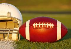 Jalkapallo ja kypärä kentällä Kuvituskuvat