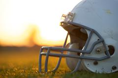 Amerikkalainen jalkapallo kypärä kenttä auringonlaskun aikaan Kuvituskuvat