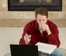 Mature man drinking water while working on assignments at home Stock Photos