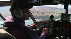 A pilot of water bomber in cockpit over lake Stock Footage
