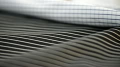 Pan shot of fabrics with measuring instrument in textile factory - stock footage