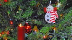 Red candle, snowman, Christmas decorations in background Stock Footage