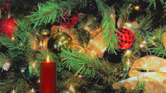 Red holiday candle with  Christmas tree decorations in background Stock Footage