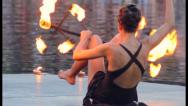 Stock Video Footage of Female fire artist handles burning flame stick with legs sitting, click for HD