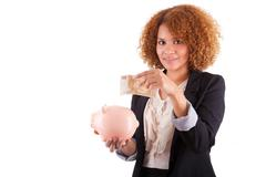 young african american business woman holding a piggy bank - african people - stock photo