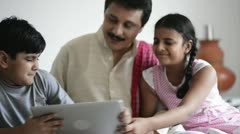 Children fighting for a laptop with their father sitting near them Stock Footage