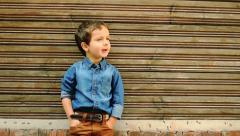 Cute three year old boy posing against wooden house wall Stock Footage