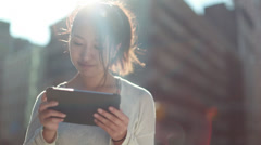 Asian woman using iPad on a city street Stock Footage