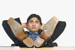 Businessman with feet up on a desk Stock Photos