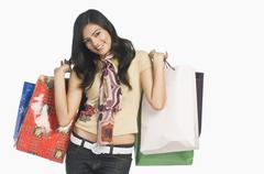 Woman carrying shopping bags and smiling Stock Photos