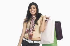 Stock Photo of Woman carrying shopping bags and smiling