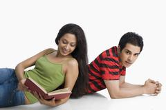 Woman leaning on a man's back and reading a book Stock Photos