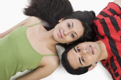 High angle view of a couple lying on the floor and smiling - stock photo